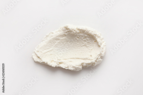 Smear of tasty cream cheese on white background, top view