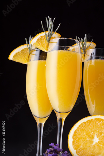 Three mimosa cocktails in champagne glasses