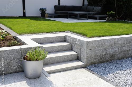 Poster Tuin Gepflegter Ziergarten mit Granitmauer und Blockstufentreppe