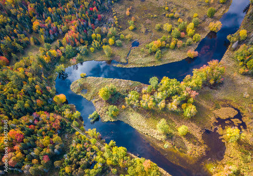 Photo Low level aerial photograph featuring fall foliage in the Adirondack Park of New York State featuring peak fall foliage colors near Saranac Lake, NY and the Saranac River