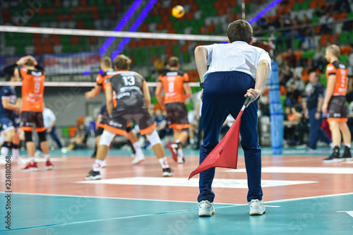 Volleyball assistant of referee with the flag observes game.