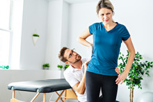 A Modern Rehabilitation Physiotherapy Man At Work With Woman Client Working On Hip
