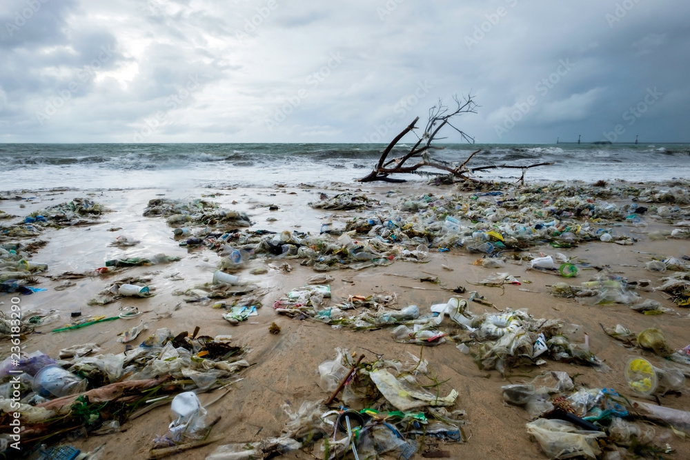 Fototapeta Garbage on beach, environmental pollution in Bali Indonesia. Drops of water are on camera lens. Dramatic view