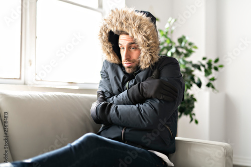 A Man have cold on the sofa at home with winter coat Fototapet