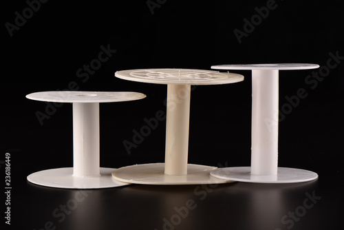Fotografija  Three plastic empty spools of tape or strips of cloth on a black