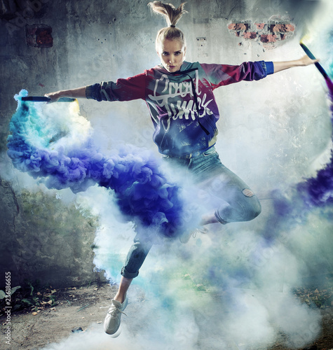 Foto op Canvas Artist KB Portrait of a jumping dancer holding colorful flares