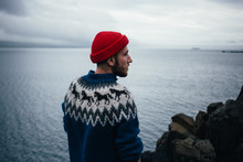 Young Handsome Man With Beard Wears Traditional Authentic Blue Wool Knitted Sweater With Ornaments And Red Fisherman Or Sailor Beanie Hat, Looks To Horizon, Pensative And Thoughtful