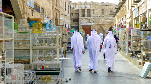 Fényképezés  Three men in traditional Qatari dress walk between bird cages and animals for sa