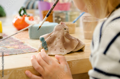 A child paints his clay figurine in a workshop at a modeling lesson.