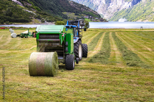 Photo Small tractor with round baler unloading on a field in Geiranger, Norway