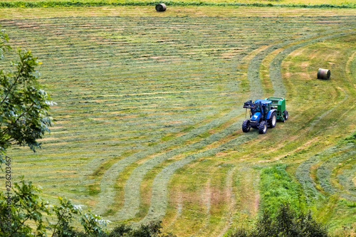 Small tractor with round baler haymaking on a field in Geiranger, Norway Wallpaper Mural