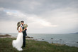 canvas print picture - young couple bride groom getting married wedding posed photos at seaside sea beach hairpiece flowers bouquet church