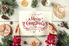 Female Hand Writing A Letter To Santa. Christmas Fir Branches With Holiday Book, Pencil, Pine Cones, Gifts On White Background. Xmas And Happy New Year Theme. Flat Lay, Top View
