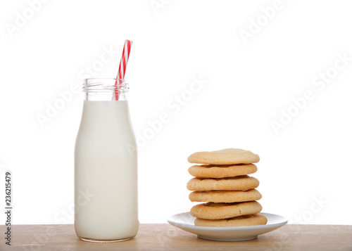 Fotografie, Obraz  Small glass bottle of fresh milk with candy cane pattern striped straw on table next to stack of homemade sugar cookies on a plate