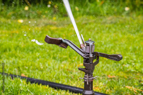 Close Up Of Sprinkler Spraying Water On A Field Lawn