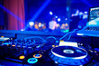 canvas print picture - DJ turntable console mixer controlling with two hand in concert nightclub stage.