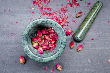 Green Marble Mortar And Pestle With Dried Pink Rosebuds Ready For Grinding