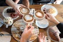 Friends With Desserts And Coffee, Close Up.Happy Couple Sitting Around The Table. Hands Holding Cups, Happy Festive Moment, Luxury Celebration Concept.