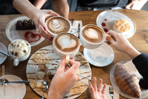 Fototapeta Friends with desserts and coffee, close up.Happy couple sitting around the table. Hands holding cups, happy festive moment, luxury celebration concept. obraz
