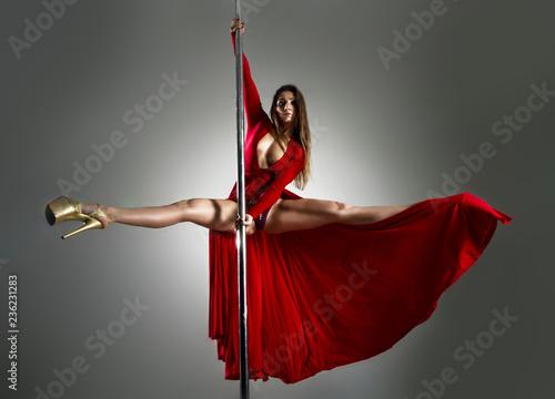 Fototapeta Slim sexy woman in a red dress dancing on a pylon obraz