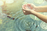 hands in cupped form getting water from a lake or fountain