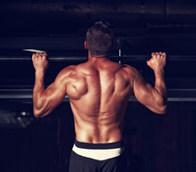 Athlete Muscular Fitness Man With Wide Tan Back Doing The Pull Up Exercises On Dark Shadow Background. Back View. Closeup Toned Portrait