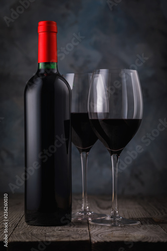 Bottle of red wine and two full glasses on a wooden table closeup