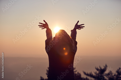Photo Woman with arms wide open enjoying the sunrise / sunset time.