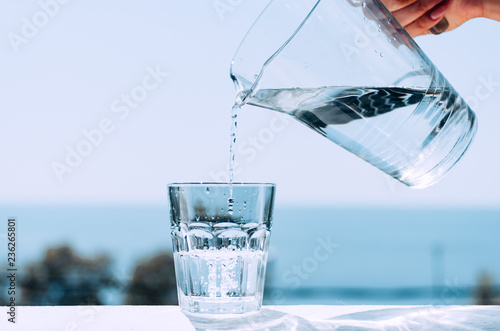 Papiers peints Eau Pure water from a jug is poured into a glass beaker. Glass with water on the background of the sea.
