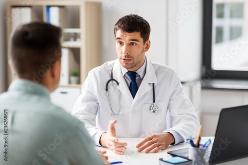 medicine, healthcare and people concept - doctor talking to male patient at medi Fototapet