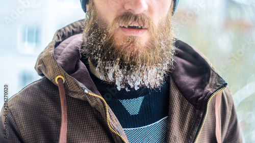 Vászonkép Part of the face of a serious and worried man is an icy beard with hanging icicles