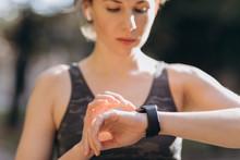 Fitness Woman In Wireless Earphones Using Smartwatch