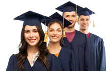 Education, Graduation And People Concept - Group Of Happy Graduate Students In Mortar Boards And Bachelor Gowns Over White Background