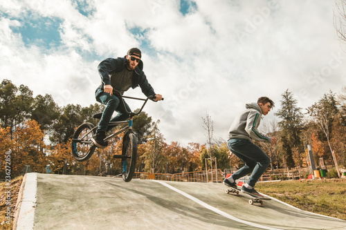 Young skateboarders and bmx bikes. Young people practicing urban sports.