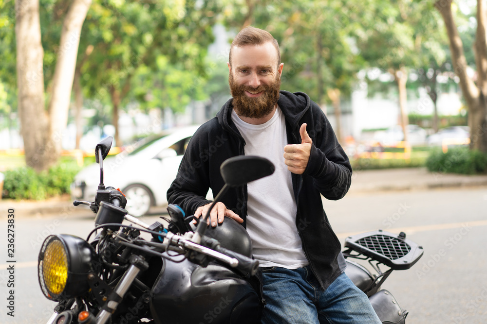 Fototapeta Portrait of happy biker sitting in motorcycle showing thumbs up. Young Caucasian man posing on his motorbike outdoors. Biker culture concept