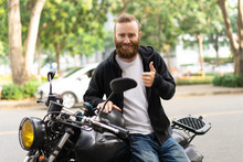 Portrait Of Happy Biker Sitting In Motorcycle Showing Thumbs Up. Young Caucasian Man Posing On His Motorbike Outdoors. Biker Culture Concept