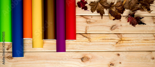Fotomural Panned colorful vinyl rolls on wooden background placed in a row with autumn lea