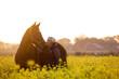 Frau mit Pferd im Rapsfeld