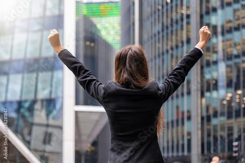 Obraz na plátně Jubelnde Gechäftsfrau im Anzug mit gestreckten Armen vor modernen Bürogebäuden