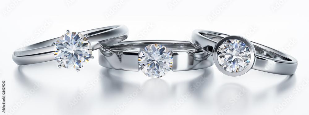 Fototapety, obrazy: 3 Solitär-Diamantringe liegend auf Weiß