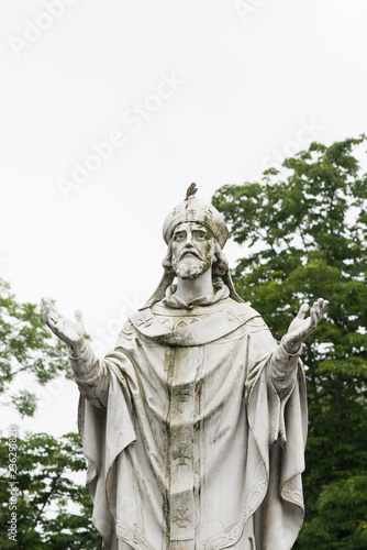 Photo  A sparrow perches on a statue of a priest