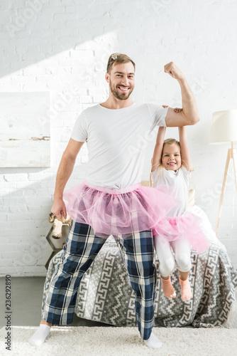 happy father and adorable little daughter in pink tutu skirts dancing and having Billede på lærred