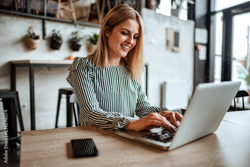 Pinturas sobre lienzo  Smiling woman typing on laptop indoors.
