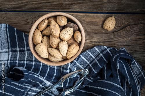 Fotobehang Kruiderij Almonds in-shell in wooden bowl.