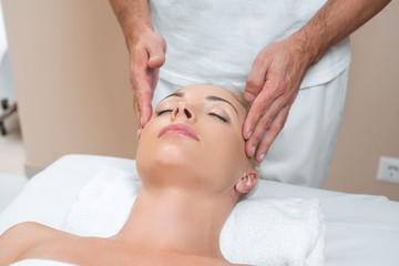 Fototapeta na wymiar Male masseur doing face massage to woman in spa salon