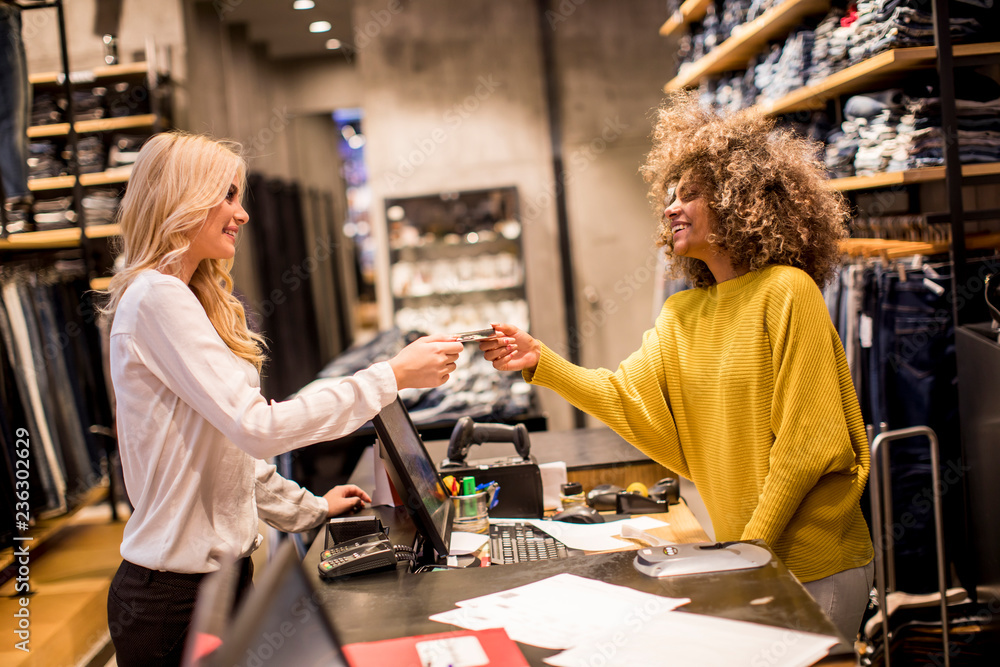 Fototapeta Attractive woman customer paying with credit card in fashion showroom