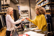canvas print picture - Attractive woman customer paying with credit card in fashion showroom
