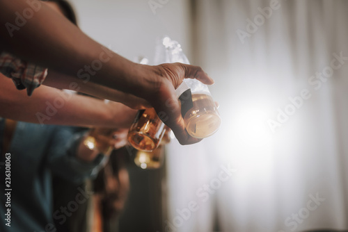 Tuinposter Bier / Cider Cheers. Close up of male and female hands holding cold tasty beer and toasting