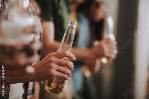 Tuinposter Bier / Cider Tasty beverage. Close up of female hand holding bottle of beer. Copy space in right side