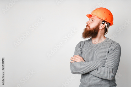 Young brutal construction worker in hard hat on a white background Canvas-taulu